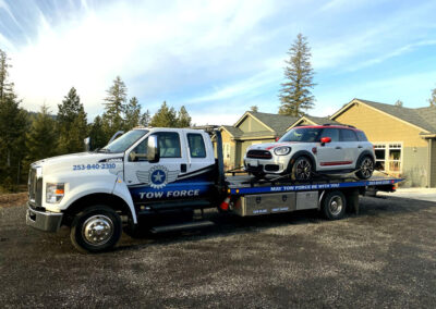 Mini Cooper loaded for transport from Spokane to Seattle for authorized repair services.