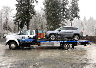 SUV being moved across Puyallup for autobody repair services.